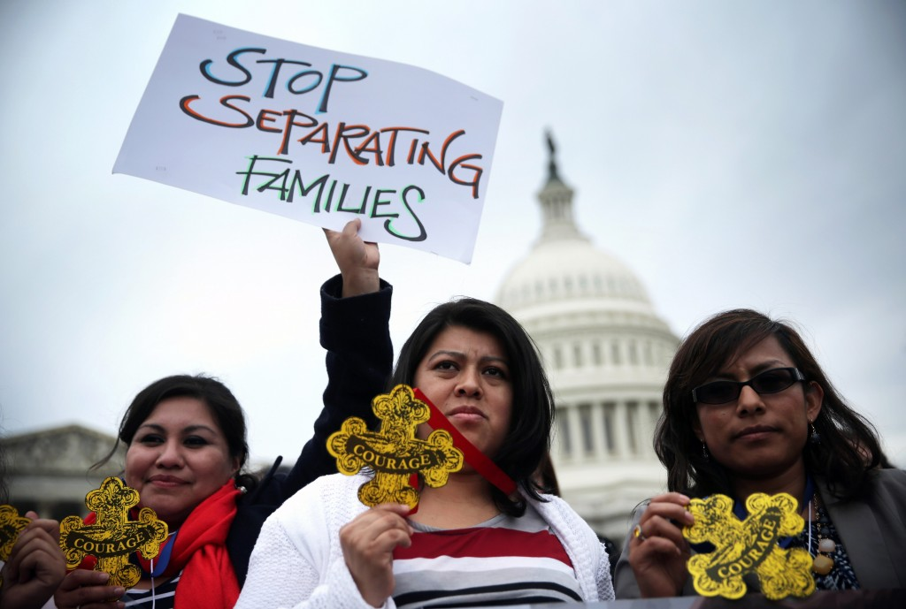 "Natividad Gonzalez (C) of Clanton, Ala., and other immigration reform activists holds signs and ""Badges of Courage"" during a news conference at the east front of the U.S. Capitol March 11, 2014 on Capitol Hill in Washington, D.C. Photo by Alex Wong/Getty Images"