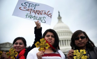 "Natividad Gonzalez of Clanton, Ala., and other immigration reform activists hold signs and ""Badges of Courage"" during a news conference at the east front of the U.S. Capitol in Washington, D.C. Photo by Alex Wong/Getty Images"
