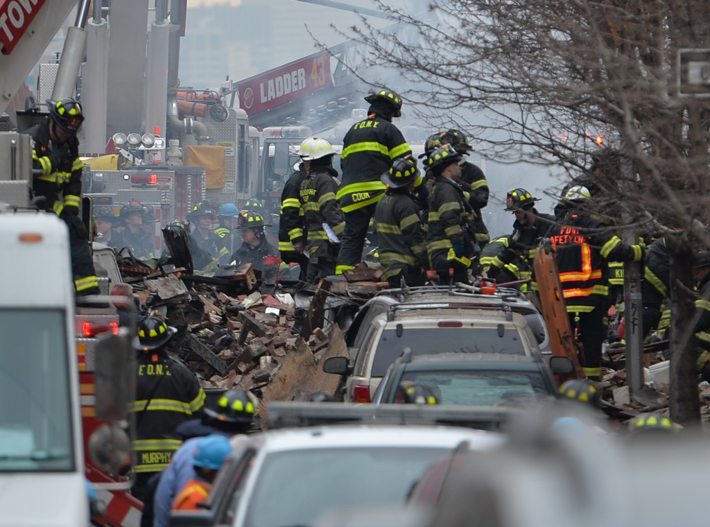 New York City Fire Department firefighters at the scene of an explosion and building collapse at Park Avenue and East 116th Street March 12, 2014 in the Harlem section of New York. A residential building exploded and collapsed on Wednesday, sparking a serious fire and engulfing the area in thick smoke, officials said. Photo by Stan Honda/AFP/Getty Images
