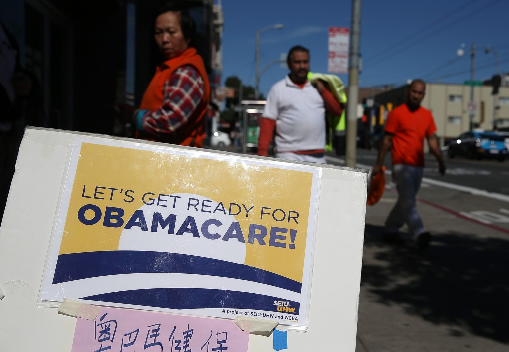 Pedestrians walk by a sign posted outside of a healthcare enrollment fair on March 18, 2014, in San Francisco. Photo by Justin Sullivan/Getty Images