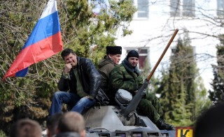 Pro-Russian self-defense activists sit on an armed personnel carrier, APC, after they seized the Ukrainian navy headquarters in the Crimean city of Sevastopol. Viktor Drachev/AFP Photo