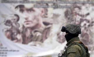 A Russian soldier stands in front of a recruitment poster for the Ukrainian armed forces in an area surrounding the Ukrainian military unit in Perevalnoye, outside Simferopol in Crimea, on March 20, 2014. Photo by Filippo Monteforte/AFP/Getty Images