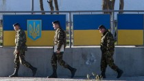 Russian officers walk past the Ukrainian marine battalion headquarters in the Crimean city of Feodosia on March 23, 2014. Ukraine's Western-backed leaders voiced fears on Sunday of an imminent Russian invasion of the eastern industrial heartland following the fall of their last airbase in Crimea to defiant Kremlin troops. AFP PHOTO/ DMITRY SEREBRYAKOV        (Photo credit should read DMITRY SEREBRYAKOV/AFP/Getty Images)