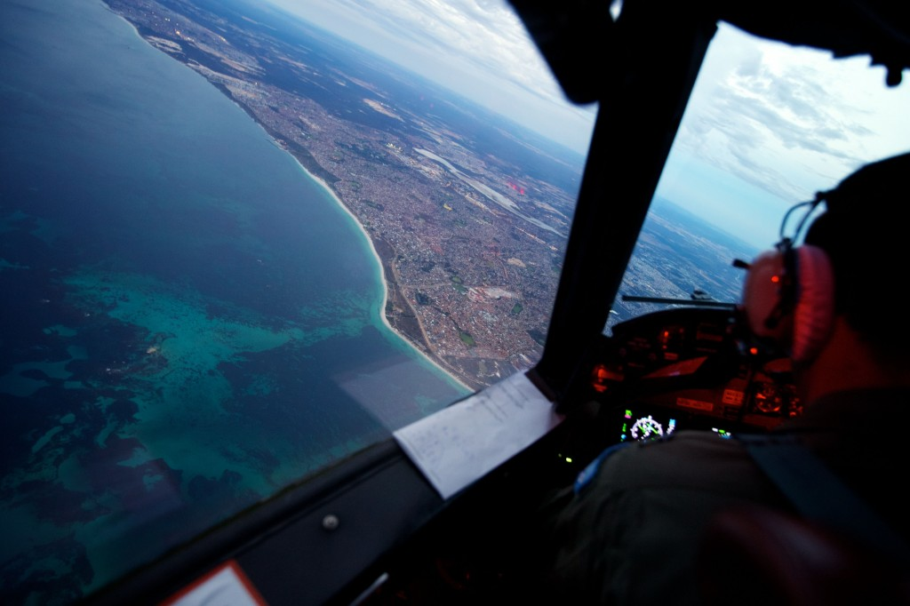 Crew on board an RAAF AP-3C Orion crossing the coast of Perth, having just completed an 11 hour search mission for missing Malaysia Airways Flight MH370, before landing at RAAF Pearce airbase in Perth, Monday, March 24, 2014. AAP Image/Richard Wainwright
