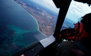 Crew on board an RAAF AP-3C Orion crossing the coast of Perth, having just completed an 11 hour search mission for missing Malaysia Airways Flight MH370, before landing at RAAF Pearce airbase in Perth, Monday, March 24, 2014. The search is being conducted in an area 2,500km off the South West coast of Perth after the Malaysian Airways aircraft went missing on March 8, 2014 whilst on a flight between Kuala Lumpur and Beijing. (AAP Image/Richard Wainwright) NO ARCHIVING