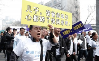 Chinese relatives of the flight MH370 march towards the Malaysian Embassy on March 25, 2014 in Beijing, China. Photo by Lintao Zhang/Getty Images