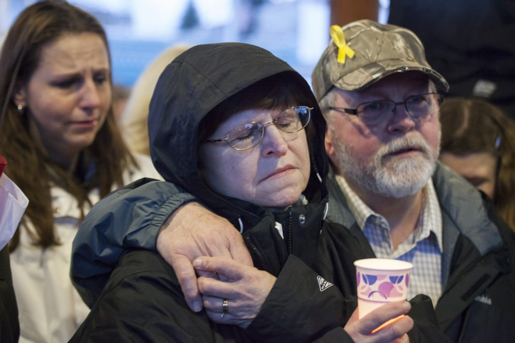 Jennifer Johnson and her parents, Gail and Ron Thompson, attend a candlelight vigil for mudslide victims on March 25, 2014 in Arlington, Washington. (Photo by David Ryder/Getty Images