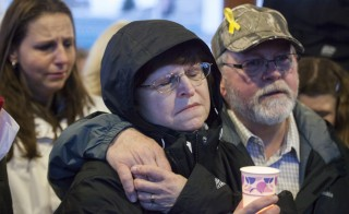 Jennifer Johnson and her parents, Gail and Ron Thompson, and attend a candlelight vigil for mudslide victims on March 25, 2014 in Arlington, Washington. (Photo by David Ryder/Getty Images