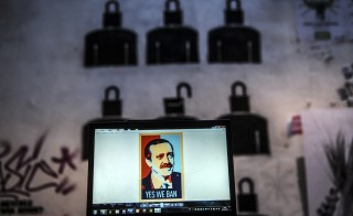 "A view of a computer screen showing a digital portrait of the Turkish Prime Minister and text reading ""Yes we ban."" Photo by Ozan Kose/AFP/Getty Images"