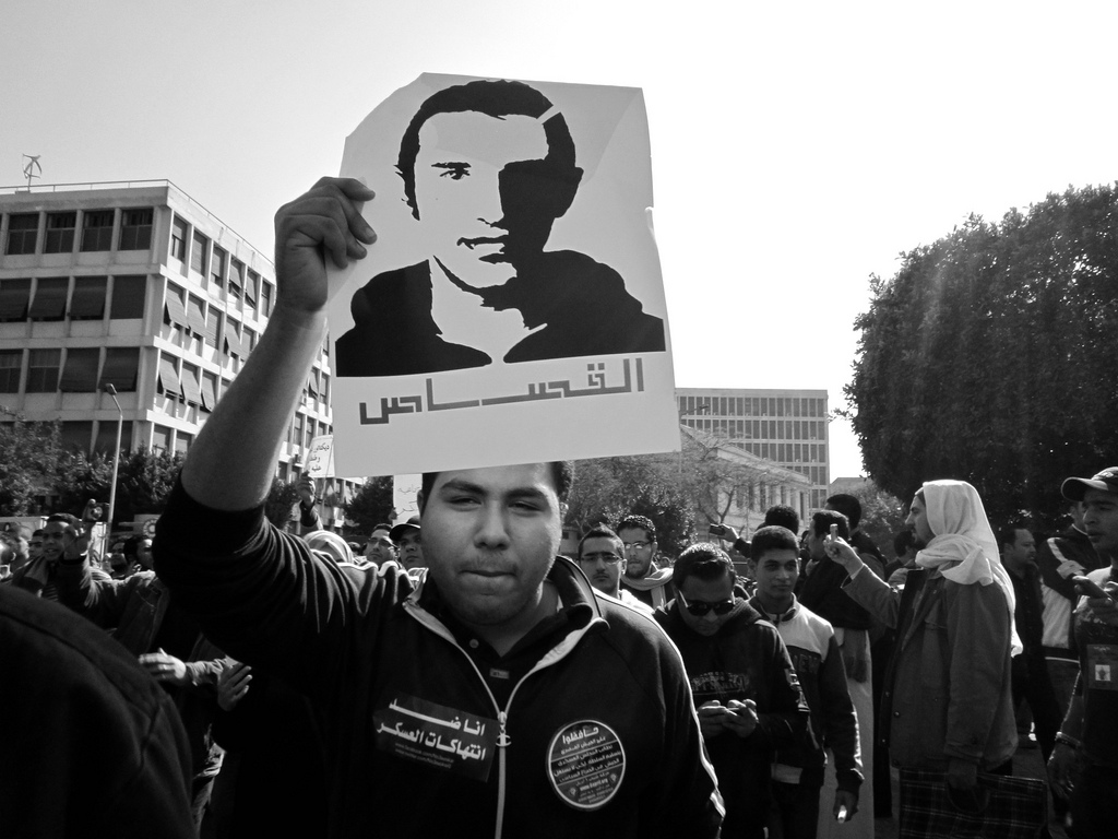 "Following his death at the hands of two Alexandrian police officers, Egyptian blogger Khaled Said became a symbol for protesters across the country. At a 2012 protest, an activist holds a sign emblazoned with Said's image, along with the word ""Retribution.""  The two officers were sentenced to ten years in jail for Said's death on Monday. Photo by Egyptian activist Gigi Ibrahim."