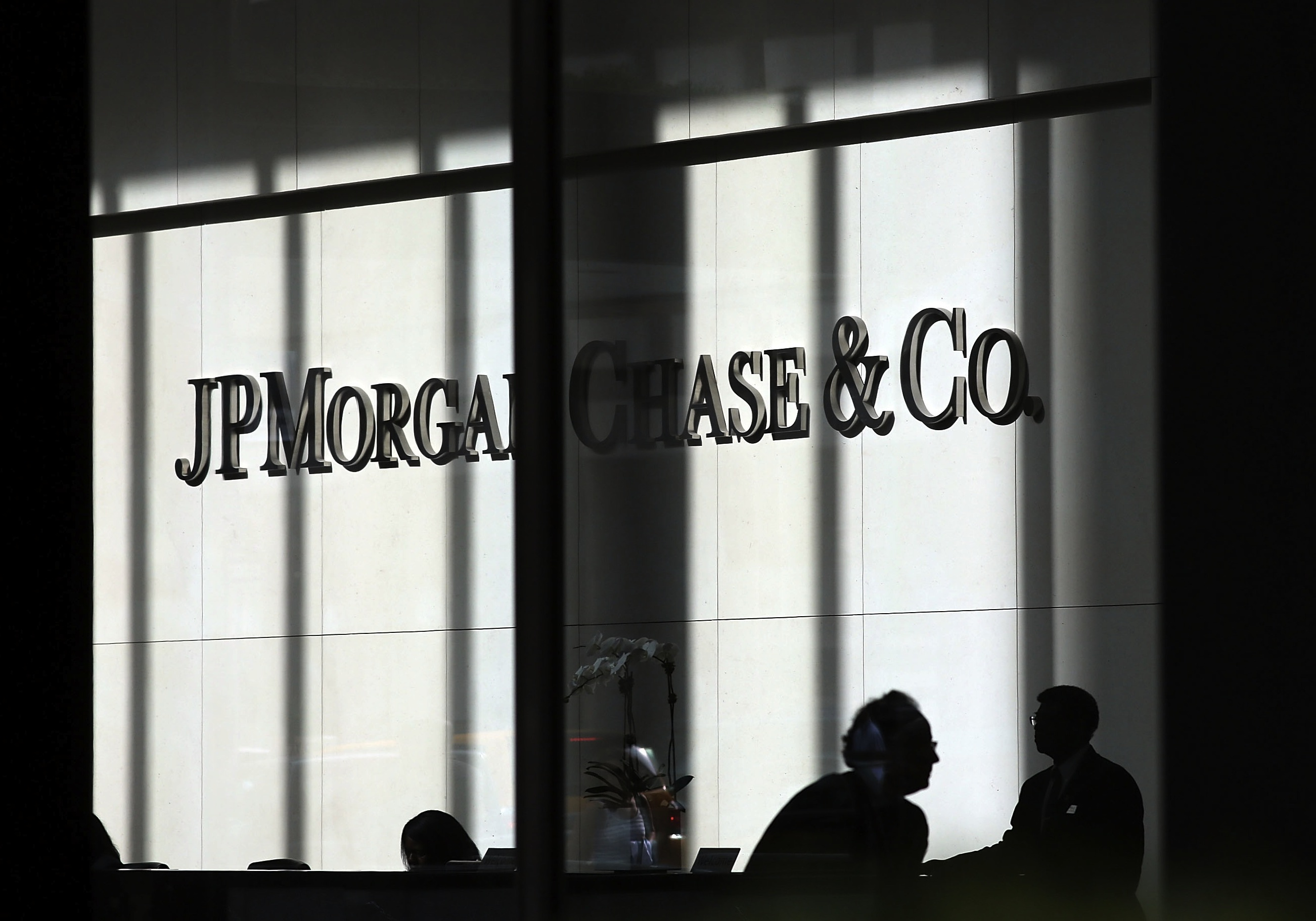 "Twenty nine out of 30 banks passed the Federal Reserve's ""stress test,"" demonstrating that big banks in the U.S. have enough capital to withstand a severe economic downturn. People pass a sign for JPMorgan Chase & Co. at its headquarters in Manhattan in New York City. Photo by Spencer Platt/Getty Images"