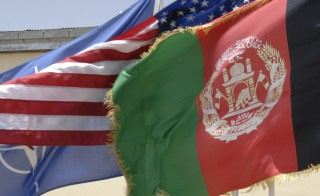 The Afghanistan, American, and Nato flag fly during change of command ceremony at Adraskan NTC, on June 16, 2011. U.S. Air Force photo by Tech Sgt. Samara Scott