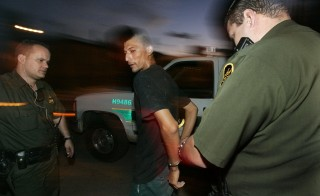 Border patrol agents detain a man suspected of crossing the border illegally in 2005 in Nogales, Ariz. Photo by Sandy Huffaker/Getty Images