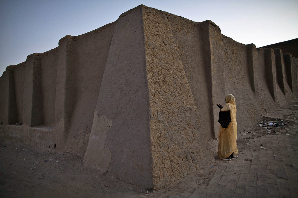 A woman prays at dawn in December 2013 outside the wall of Djingarey Berre Mosque in Timbuktu, Mali, where mausoleums were destroyed by militants the previous year. Photo by Marco Dormino/U.N. mission in Mali