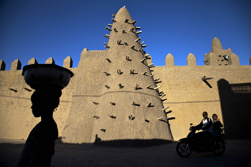 The Djingarey Berre Mosque is one of three UNESCO World Heritage mosques in Timbuktu, Mali. The wooden spikes serve as scaffolding for workers to smooth new layers of mud onto the structure. Photo by Marco Dormino/U.N. mission in Mali