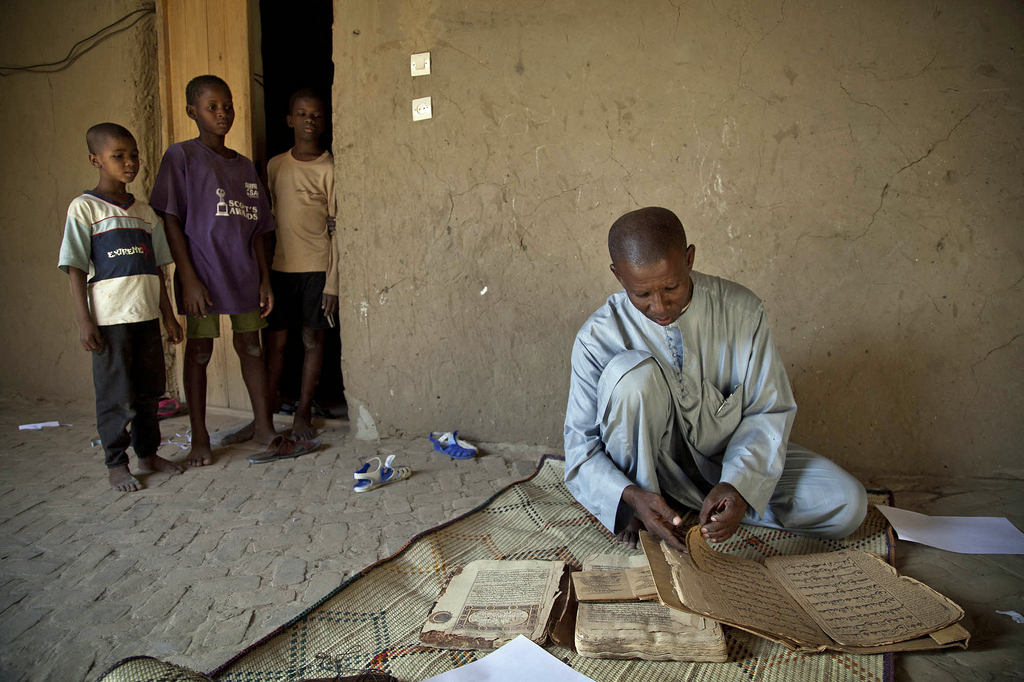 Abdul Wahid, a teacher of the Quran, shows the manuscripts that his grandfather had left to him. Like other families, he hid the ancient texts when the jihadists occupied Timbuktu. Photo by Marco Dormino/U.N. mission in Mali