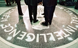 President George W. Bush, Central Intelligence Agency Director George Tenet and others stand on the seal of the Agency March 20, 2001 at the CIA Headquarters in Langley, Virginia. Photo by David Burnett/Newsmakers