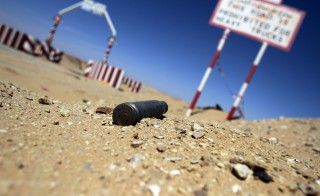 An empty bullet shell is seen outside the entrance of the al-Ghani oil field, belonging to Libya's Harouge Oil Operations company, near the city of Waddan in the central Al-Jufrah province on March 23, 2013. Photo by Abdullah Doma/Getty Images