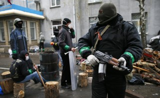 Pro-Russian armed men stand guard while pro-Russian protesters gather near the police headquarters in Slaviansk