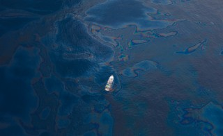 A ship floats amongst a sea of spilled oil in the Gulf of Mexico after the BP Deepwater Horizon oilspill disaster. Photo by Flickr user kris krüg