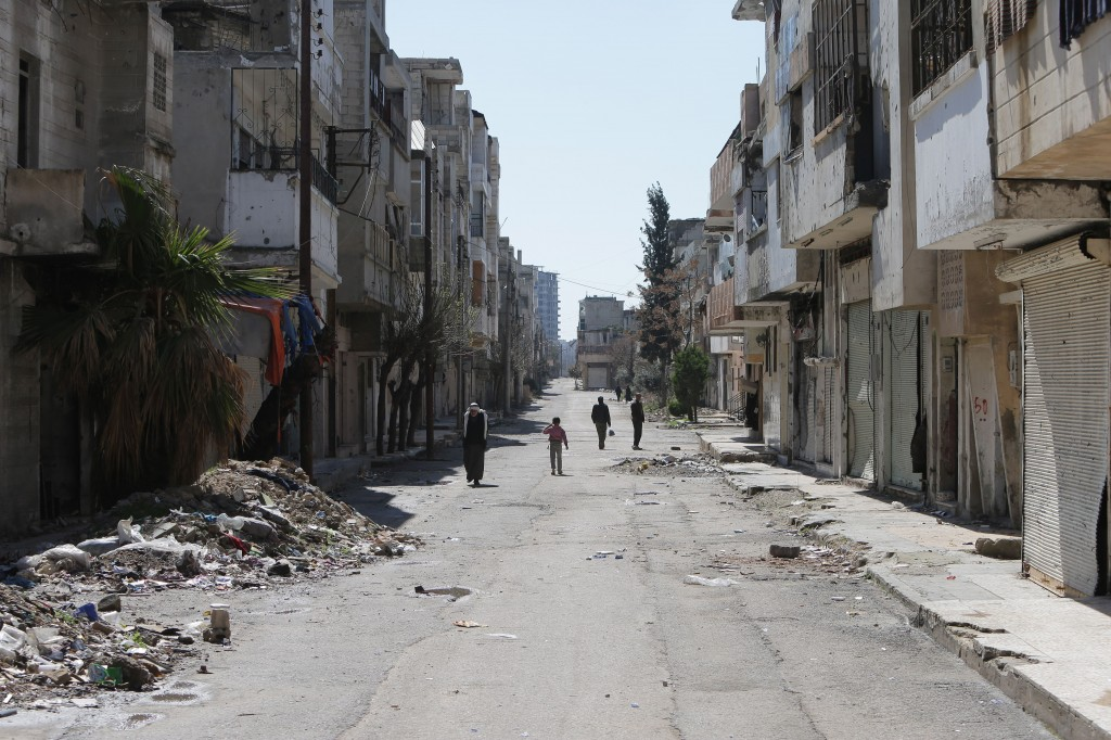 Syrians walk in the once rebel-held neighbourhood of Baba Amro in the central Syrian city of Homs on March 15, 2014. Photo by Joseph Eid/AFP/Getty Images