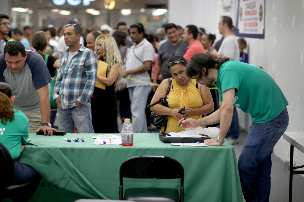 An agent from Sunshine Life and Health Advisors helps sign people up for insurance under the Affordable Care Act in Miami. Although 8 million have signed up, new polls show the health care law remains a net negative for many Americans. Photo by Joe Raedle/Getty Images