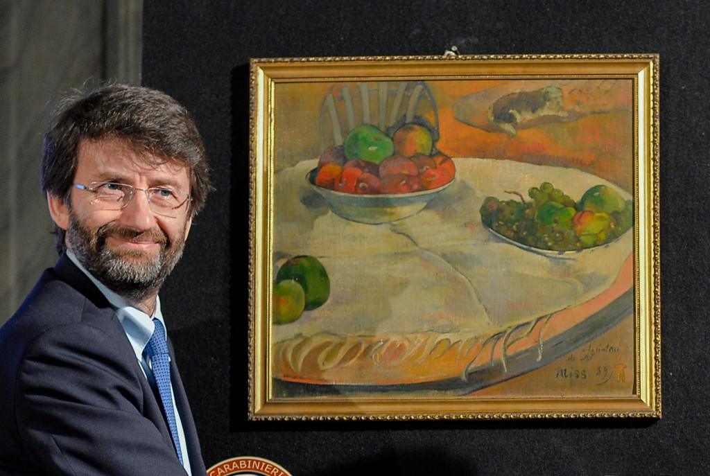 Italian Culture minister Dario Franceschini stands next to to the painting by French artist Paul Gauguin 'Fruits sur une table ou nature morte au petit chien.' Photo by ANDREAS SOLARO/AFP/Getty Images
