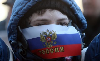 A young demonstrator with his mouth covered by a Russian flag attends a rally of pro-Russia supporters outside the regional government administration building in the center of the eastern Ukrainian city of Donetsk. Photo by Alexander Khudoteply/AFP