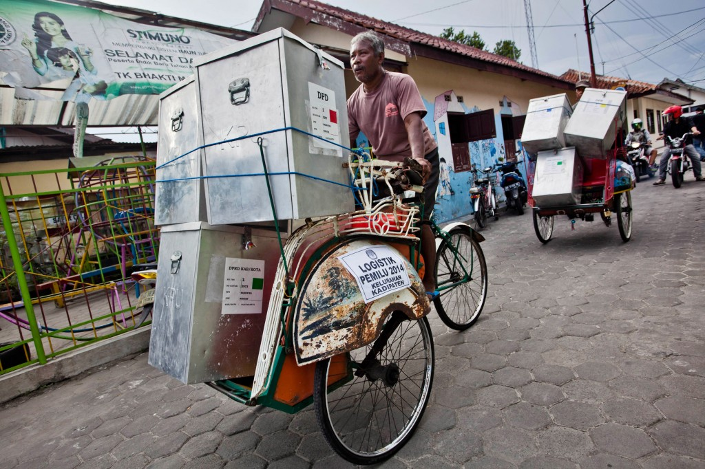 YOGYAKARTA, INDONESIA - APRIL 08:  Pedicab drivers carry ballot boxes for distribution to polling station during prepares for Legislative Election on April 8, 2014 in Yogyakarta, Indonesia. The Indonesian legislative election will be held on April 9, 2014, with the presidential election set to follow three months later on July 9, 2014.  (Photo by Ulet Ifansasti/Getty Images)
