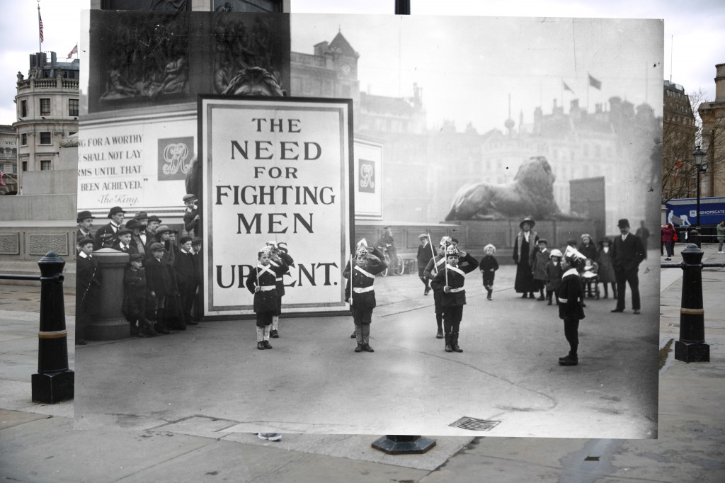 In Trafalgar Square, London, street urchins dressed as soldiers with paper hats and canes as guns stand to attention watched by a small crowd in November, 1914. Behind them is a notice declaring 'The Need for Fighting Men is Urgent.' 1914 photo by Topical Press Agency/Getty Images. 2014 photo by Peter Macdiarmid/Getty Images