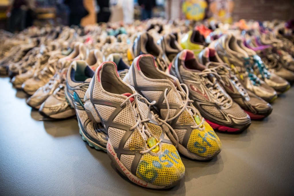Running shoes are laid out in a display at the Boston Public Library to commemorate the 2013 Boston Marathon bombings. Photo by Andrew Burton/Getty Images