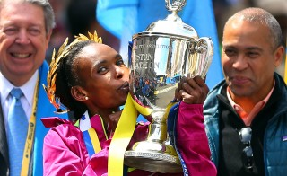 Rita Jeptoo of Kenya kisses her trophy during her victory ceremony after winning first place and setting a course record in the women's race of the 118th Boston Marathon. Photo by John Tlumacki/The Boston Globe via Getty Images