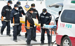 "South Korean rescue members carry the body of a victim recovered from the ""Sewol"" ferry to an ambulance at a harbour in Jindo on April 22, 2014. Photo by Jung Yeon-Je/AFP/Getty Images"
