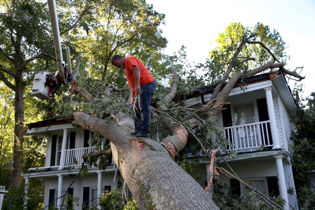 Deadly tornadoes ripped across Oklahoma, Arkansas, and Mississippi and have caused severe flooding in parts of the Florida Panhandle. Rodney Stanford works on removing a tree that is resting on a home after a tornado struck Tupelo, Mississippi, on Monday. Photo by Joe Raedle/Getty Images