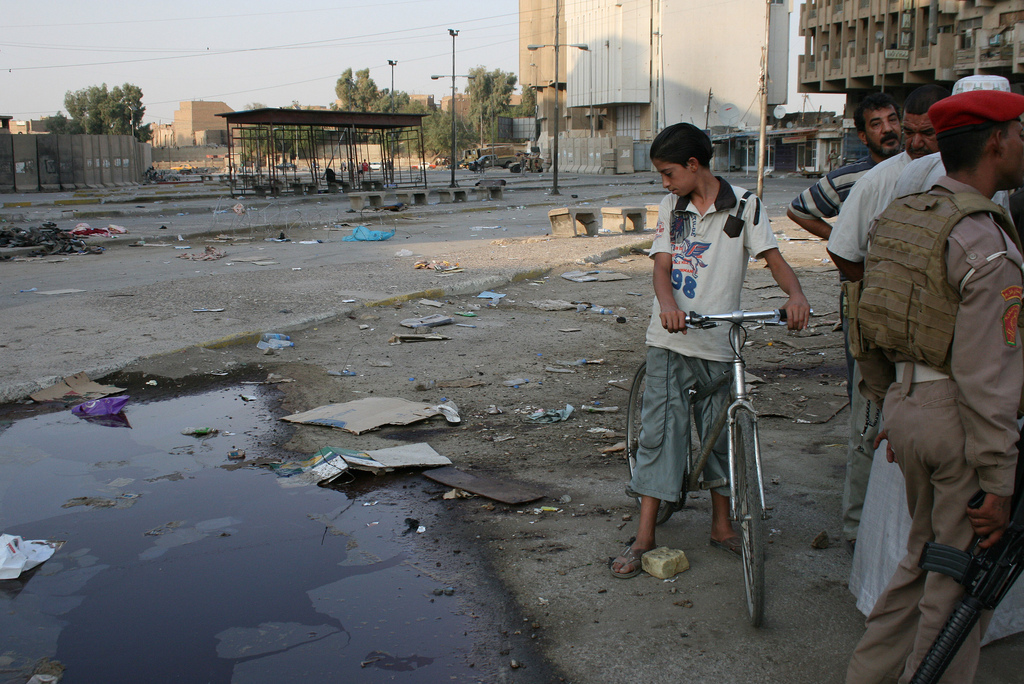 An Iraqi boy looks at a pool of blood left by a suicide bombing at the army headquarters in Baghdad on Aug. 17, 2010. Photo by Larisa Epatko