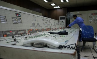 Control Room Workers, dressed in blue jumpsuits, operate switches in the control room. The Doura station powers other substations in Baghdad.