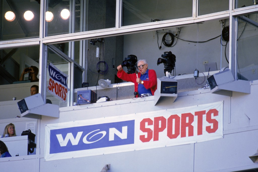 "Chicago Cubs baseball announcer and Baseball Hall of Fame inductee Harry Caray conducts fans singing ""Take Me Out to the Ball Game"" from his television booth during the seventh inning stretch in a game against the Colorado Rockies at Wrigley Field on August 2, 1996. Photo by Jonathan Daniel/Getty Images"