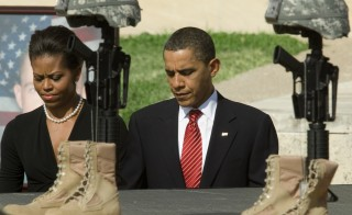 First Lady Michelle Obama and President Obama walk past the Fallen Hero Memorial at Fort Hood on November 10, 2009 during a service honoring the soldiers and civilians killed in a shooting rampage on November 5, 2009. Photo by PAUL J. RICHARDS/AFP/Getty Images