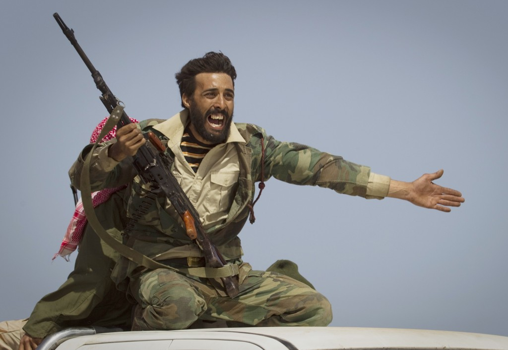 A Libyan rebel urges people to leave, as shelling from Gadhafi's forces started landing on the frontline outside of Bin Jawaad, 150 km east of Sirte, central Libya, Tuesday, March 29, 2011.  Photo by Anja Niedringhaus/AP