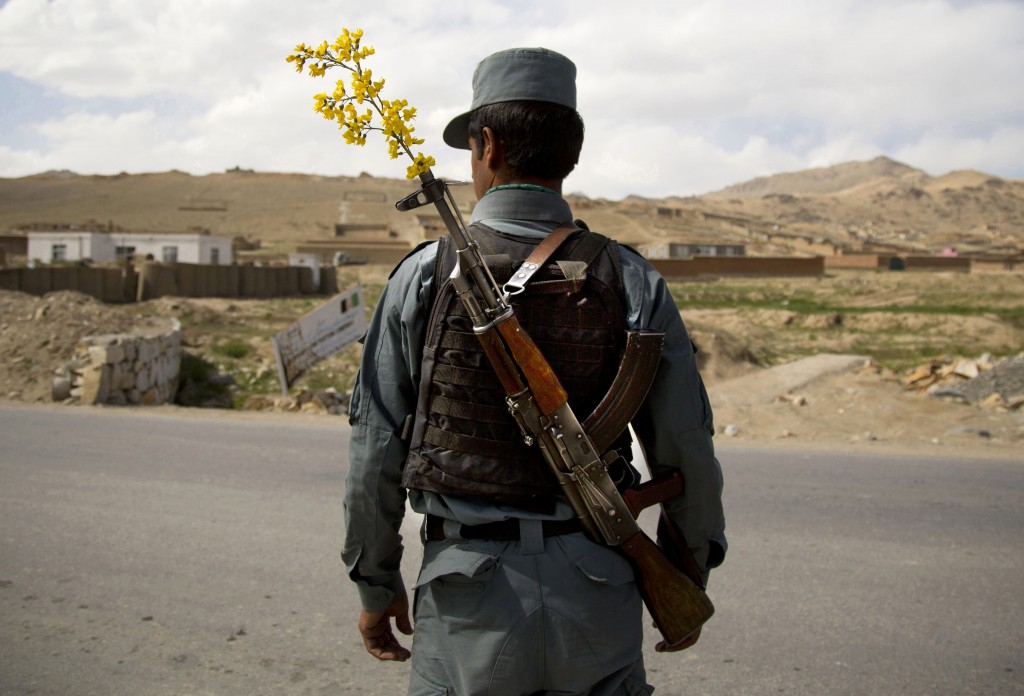 In this Wednesday, May 15, 2013 file photo made by Associated Press photographer Anja Niedringhaus, an Afghan National Police officer mans a checkpoint in the outskirts of Maidan Shahr, Wardak province, Afghanistan.
