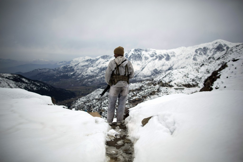 In this Friday, Feb. 17, 2012 file photo made by Associated Press photographer Anja Niedringhaus, a Pakistani Army soldier with the 20th Lancers Armored Regiment stands atop the 8000-foot mountain during a patrol near his outpost, Kalpani Base, in Pakistan's Dir province on the Pakistan-Afghan border.