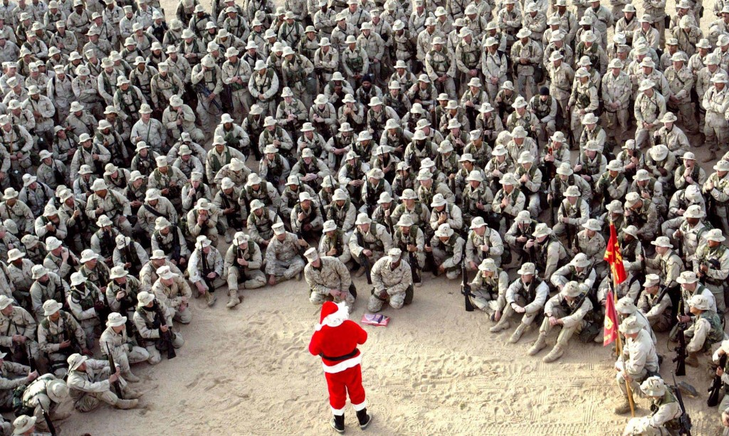 In this Tuesday, Dec. 24, 2002 file photo made by Associated Press photographer Anja Niedringhaus, hundreds of U.S. Marines gather at Camp Commando in the Kuwait desert during a Christmas eve visit by Santa Claus.