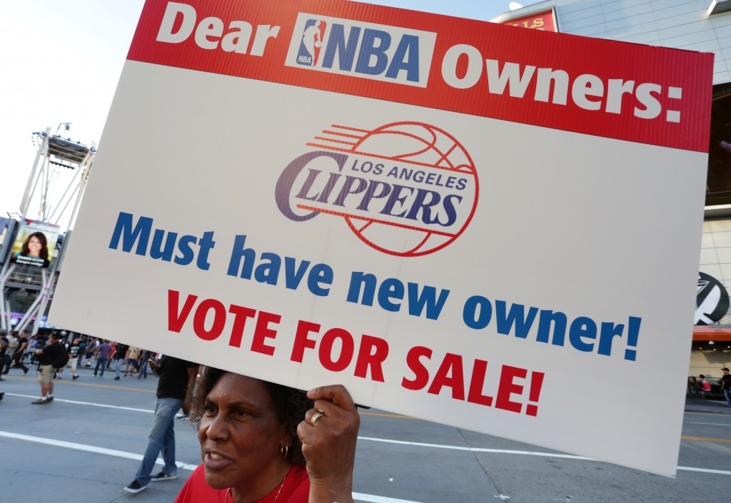 Susan Wright holds a sign protesting racist comments made by L.A. Clippers owner Donald Sterling outside Staples Center before a playoff game on April 29, 2014 in Los Angeles. Photo by Jonathan Alcorn/Getty Images.