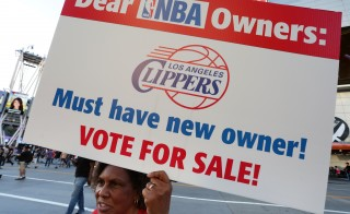 Susan Wright holds a sign protesting racist comments made by L.A. Clippers owner Donald Sterling outside Staples Center before a playoff game on April 29, 2014 in Los Angeles, California. Clippers owner Donald Sterling was banned for life today by the NBA and barred from having any association with the team and ordered to pay a $2.5 million fine. Photo by Jonathan Alcorn/Getty Images.