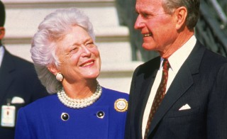 Then-President George H.W. Bush stands with first lady Barbara Bush, awaiting the arrival of Polish President Lech Walesa to Washington, D.C., on March 20, 1991. Photo by Ron Sachs/Consolidated News/Getty Images