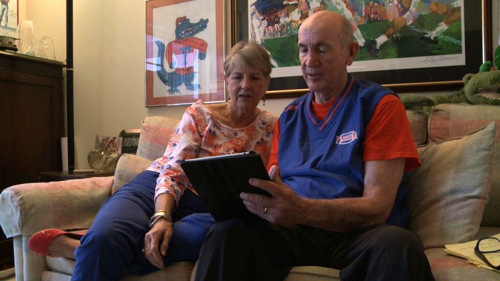 Ray and Ann Goldwire look at some of their family photos in their Gainesville, Fla., apartment, which is part of a university-based retirement community. Video still by Steve Mort/PBS NewsHour