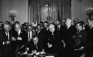 President Lyndon B. Johnson signs the 1964 Civil Rights Act as Martin Luther King, Jr. and others look on. East Room, White House, Washington, D.C. Photo by Cecil Stoughton