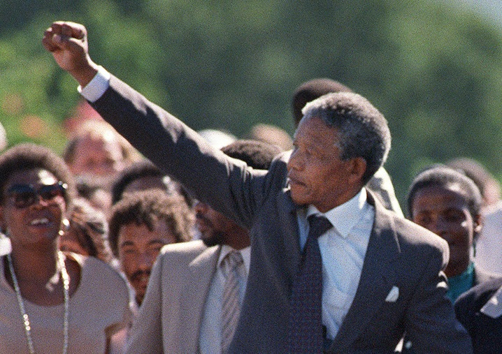 A picture taken on February 11, 1990 shows Nelson Mandela (C) and his then-wife Winnie raising their fists and saluting cheering crowd upon Mandela's release from the Victor Verster prison near Paarl. Rolihlahla Dalibhunga Mandela, affectionately known by his clan name 'Madiba', became commander-in-chief of Umkhonto weSizwe (Spear of the Nation), the armed underground wing of the African National Congress, in 1961, and the following year underwent military training in Algeria and Ethiopia. After more than a year underground, Mandela was captured by police and sentenced in 1964 to life in prison during the Rivonia trial, where he delivered a speech that was to become the manifesto of the anti-apartheid movement. Mandela started his prison years in the notorious Robben Island Prison, a maximum security prison on a small island 7Km off the coast near Cape Town. In April 1984 he was transferred to Pollsmoor Prison in Cape Town and in December 1988 he was moved the Victor Verster Prison near Paarl. While in prison, Mandela flatly rejected offers made by his jailers for remission of sentence in exchange for accepting the bantustan policy by recognising the independence of the Transkei and agreeing to settle there. Again in the 'eighties Mandela rejected an offer of release on condition that he renounce violence. Prisoners cannot enter into contracts. Only free men can negotiate, he said, according to ANC reports. AFP PHOTO FILES / ALEXANDER JOE (Photo credit should read ALEXANDER JOE/AFP/Getty Images)