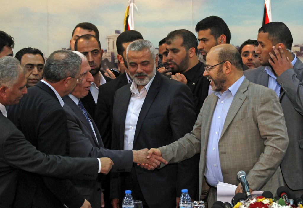 Palestinian Fatah delegation chief Azzam al-Ahmed (center-left) shakes hands with Hamas deputy leader Musa Abu Marzuk (right) in the presence of Hamas Prime Minister in the Gaza Strip Ismail Haniyeh (center), after signing a reconciliation agreement in Gaza on April 23, 2014. Photo by said Khatib/AFP/Getty Images