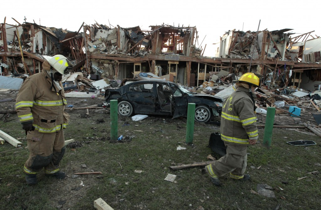 Valley Mills Fire Department personnel walk among the remains of an apartment complex next to the fertilizer plant that exploded yesterday afternoon on April 18, 2013 in West, Texas. A federal probe has found gaps in chemical safety regulations at several plants and other locations across the U.S. Photo by Erich Schlegel/Getty Images